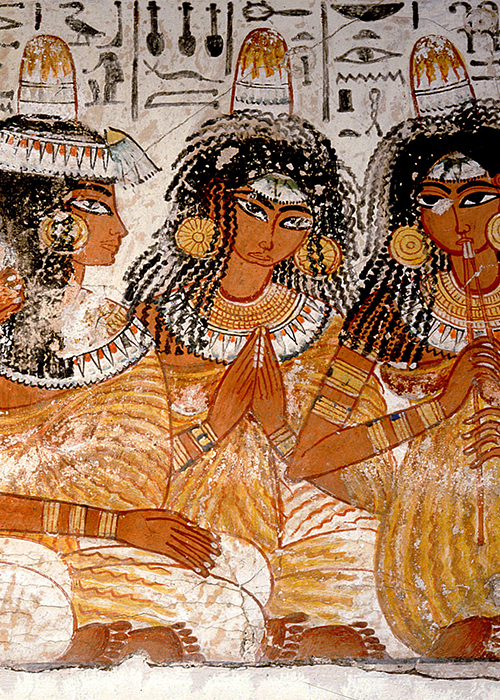Part of a banquet scene from the tomb of Nebamun, Four young women wearing pleated gowns and wigs with lotus blossoms and unguent cones play music for the banquet guests.
